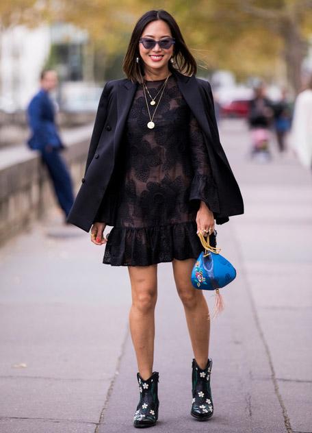 Девушка в черном платье мини, пиджак и ковбойские сапоги