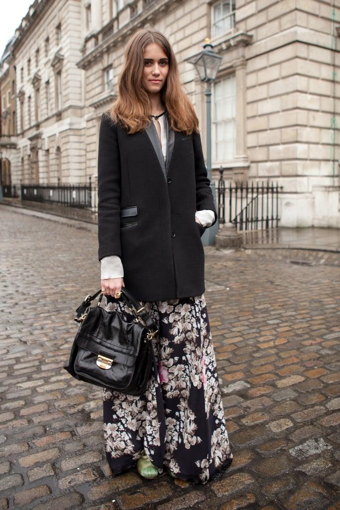 Девушка в черном цветочном платье и черное пальто