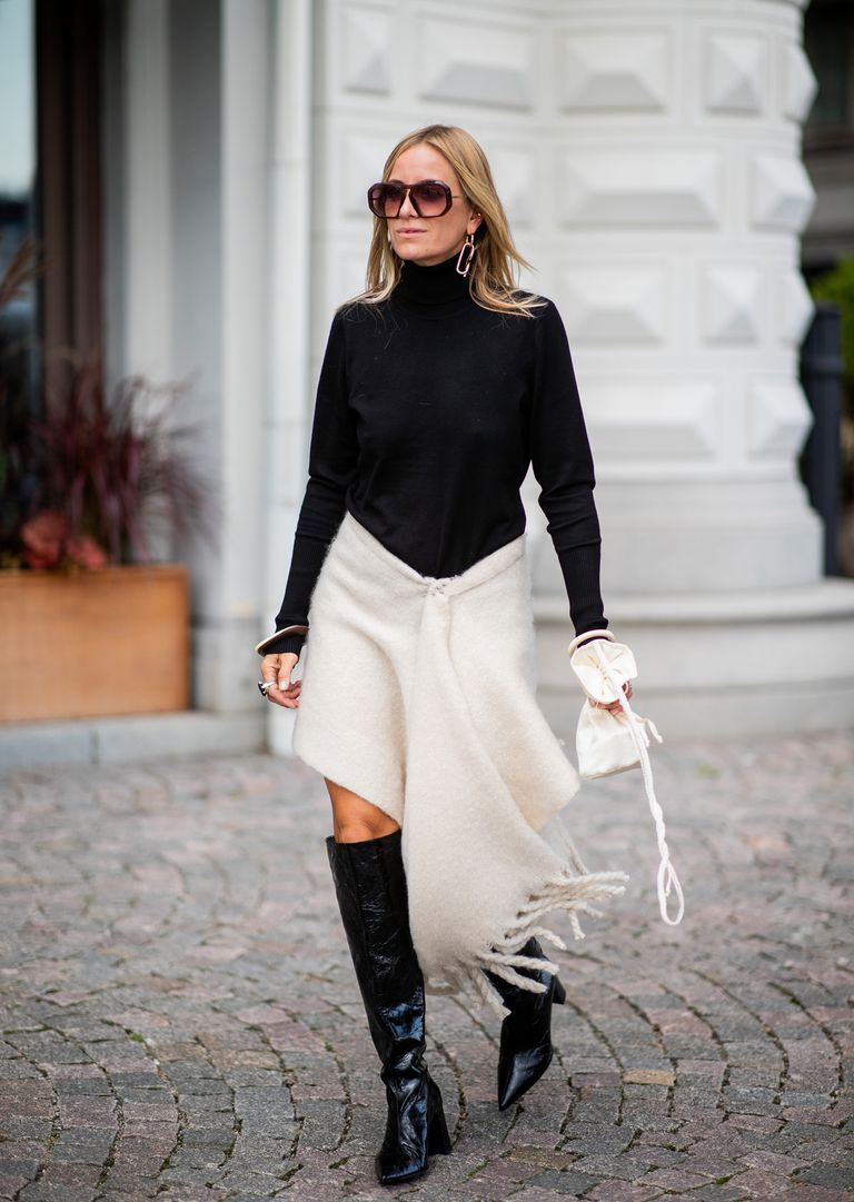 Девушка в черной водолазке, белая юбка с бахромой и высокие сапоги
