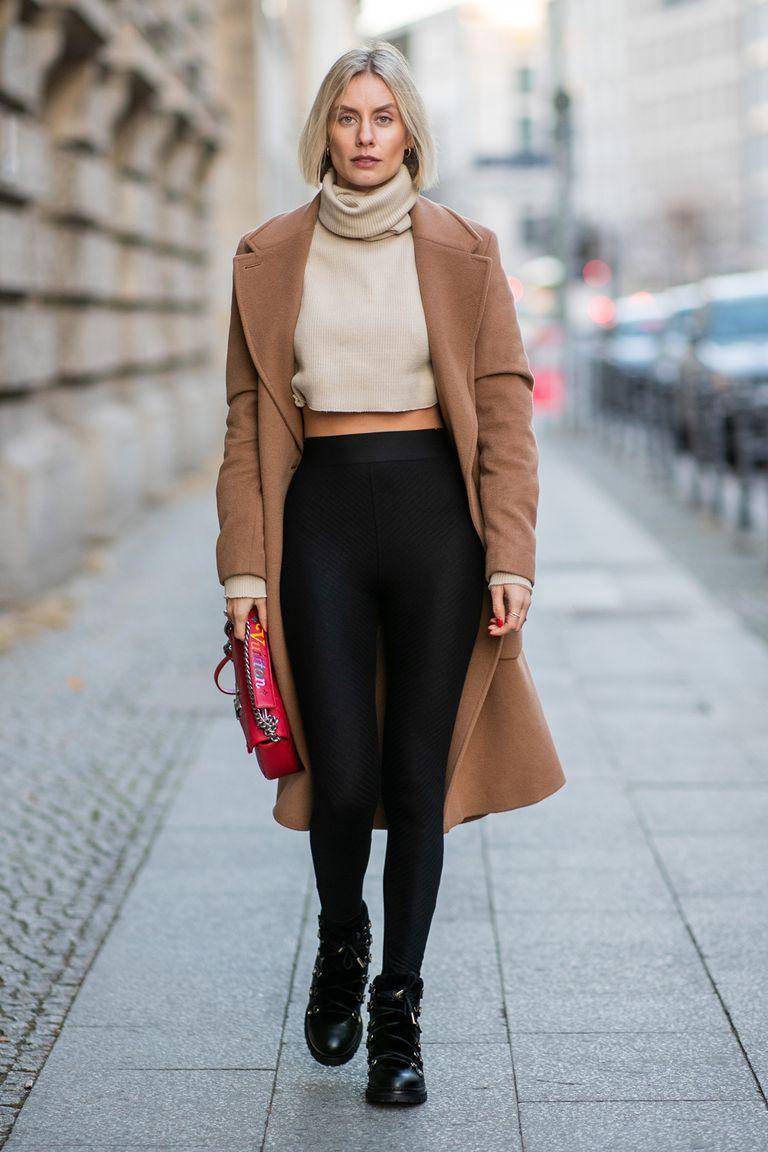 Девушка в черных леггинсах, свитер и бежевое пальто