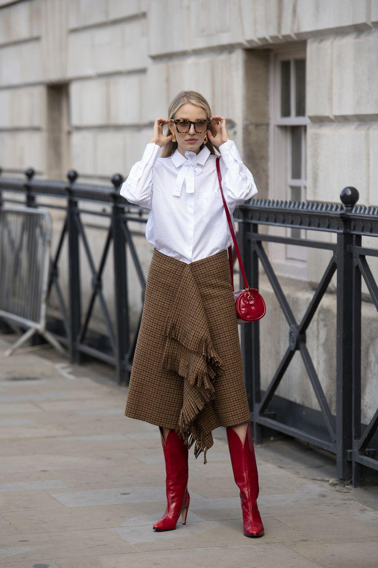 Девушка в коричневой юбке, белая блузка и красные сапоги