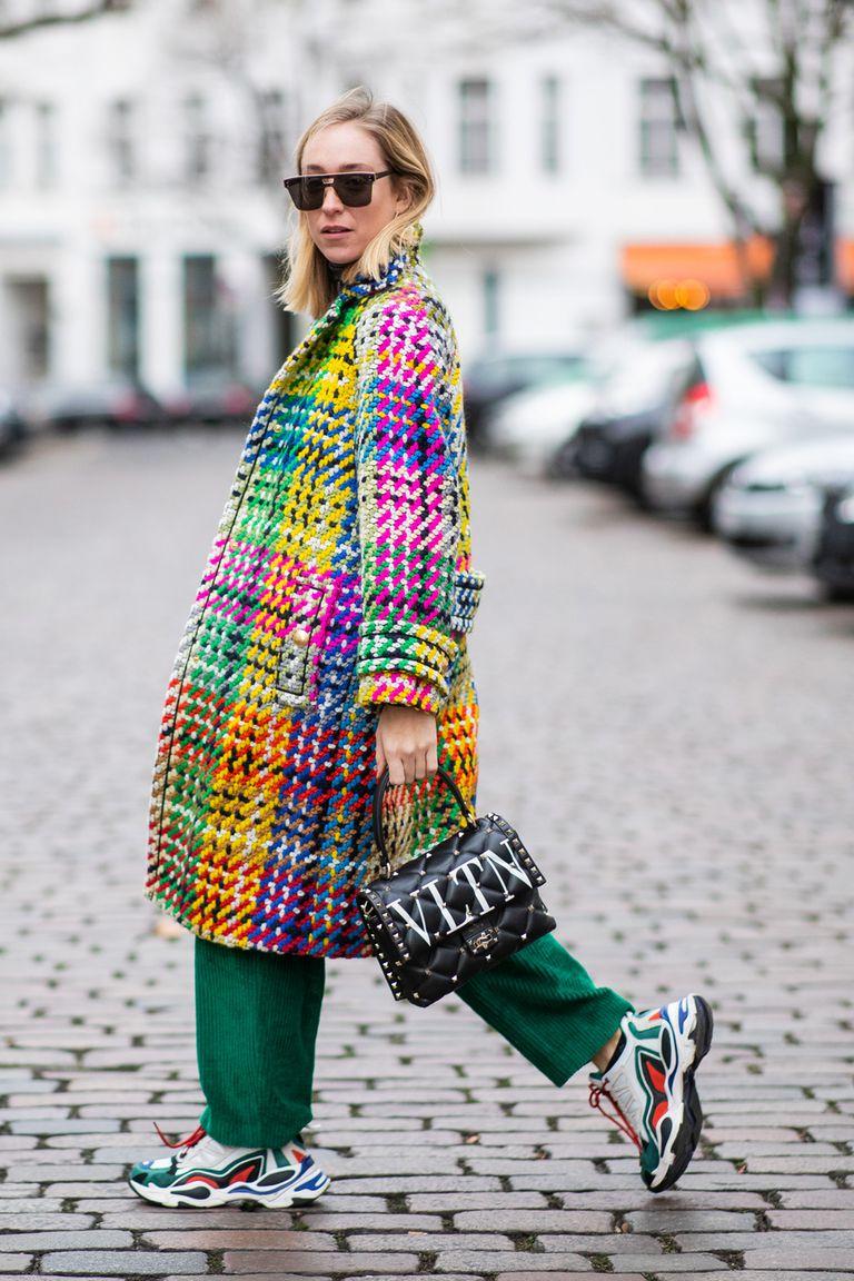 Девушка в разноцветном пальто оверсайз, зеленые брюки и кроссовки