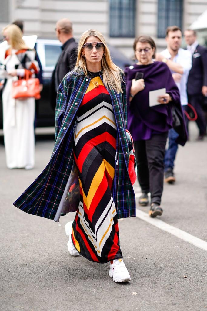 Девушка в разноцветном платье в полоску и пальто в клетку