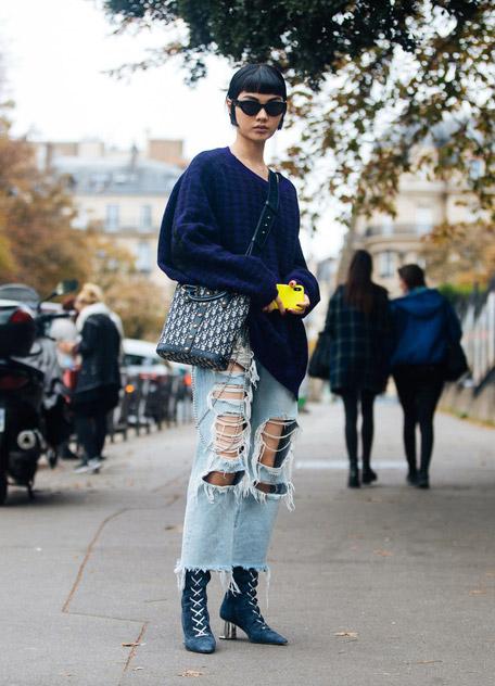 Девушка в рванных джинсах, свитер оверсайз и ботильоны