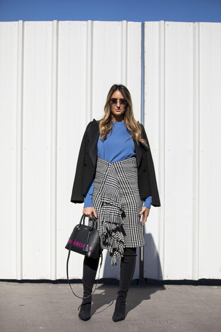 Девушка в серой юбке миди с бахромой, голубой свитшот и сапоги