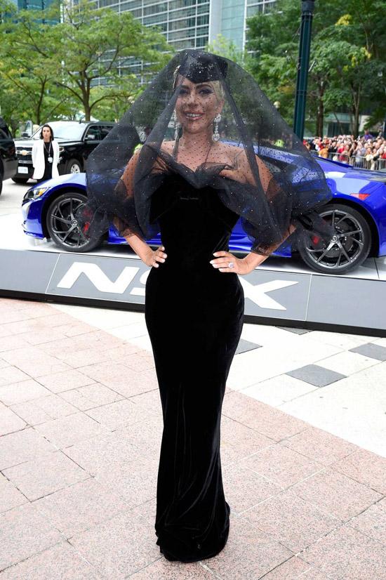 Леди Гага в черном облегающем платье и шлапка с вуалью
