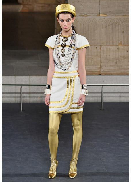 Модель в белом мини платье и золотых колготках
