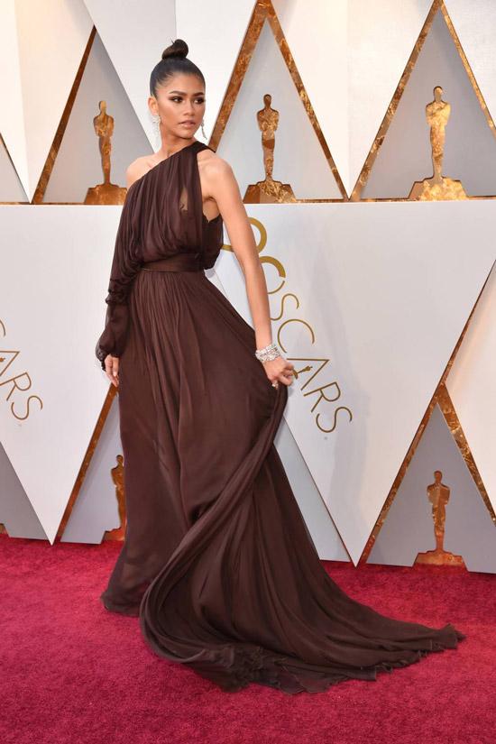 Зендая в длинном коричневом платье на одно плечо