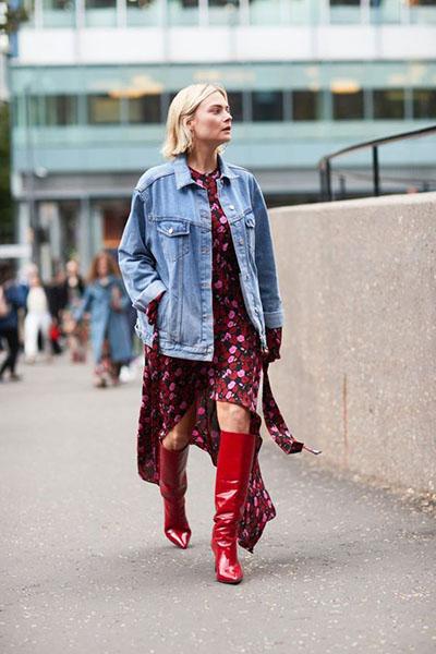 Девушка в бордовом платье с цветочным принтом, красные сапоги и джинсовая куртка