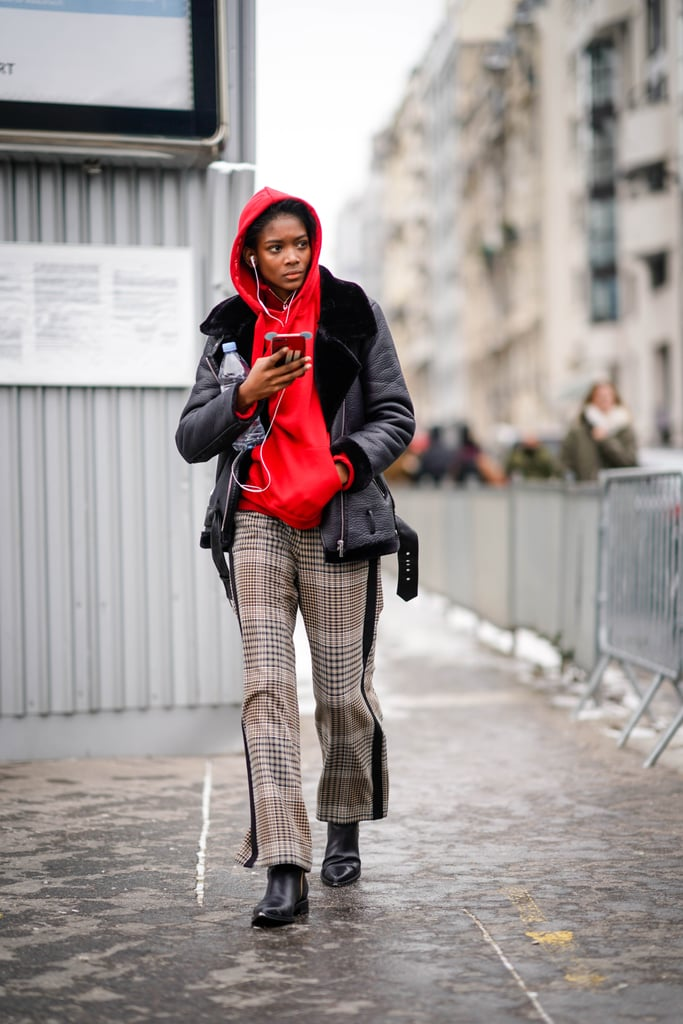 Девушка в брюках в клетку, красное худи и черная куртка