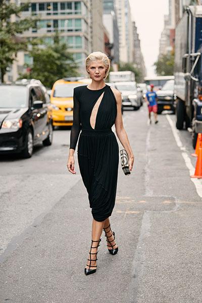 Девушка в черном ассиметричном платье миди