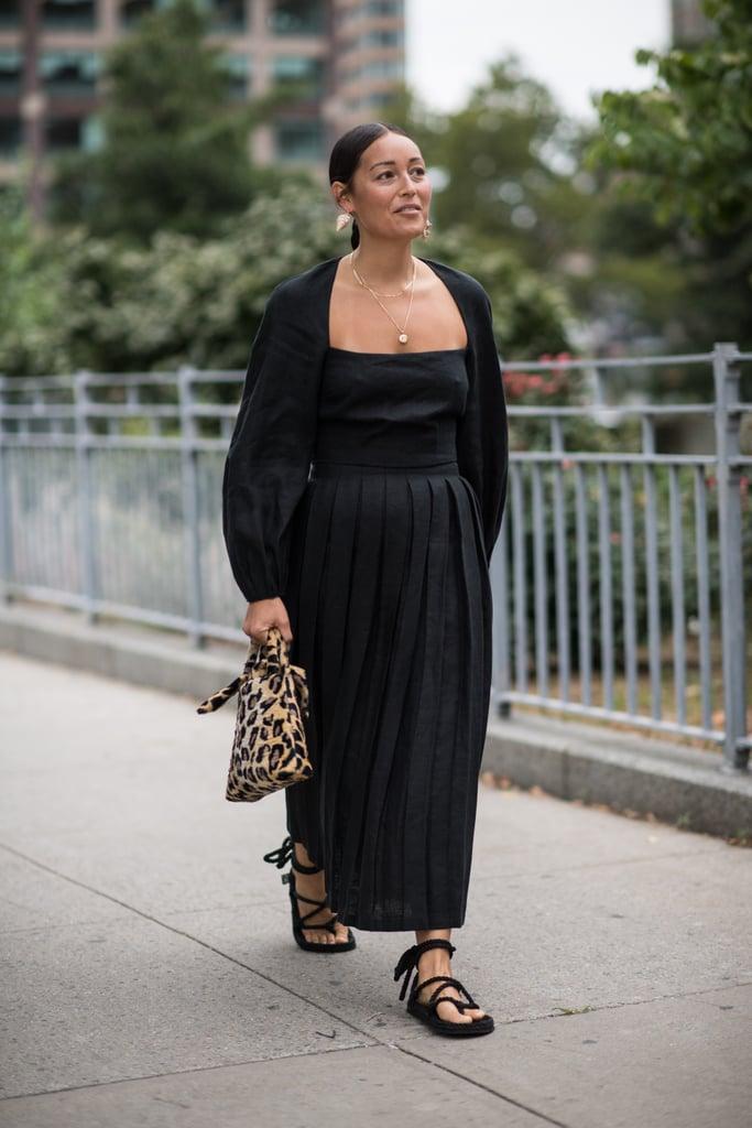 Девушка в черном платье макси, лепардовая сумочка и сандалии на плоской подошве