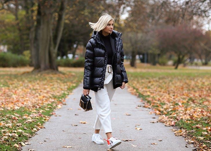Девушка в черном пуховике, белые брюки и кроссовки