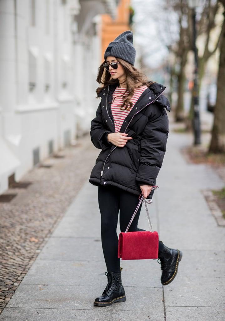 Девушка в черном пуховике, свитшот в полоску и черные ботинки