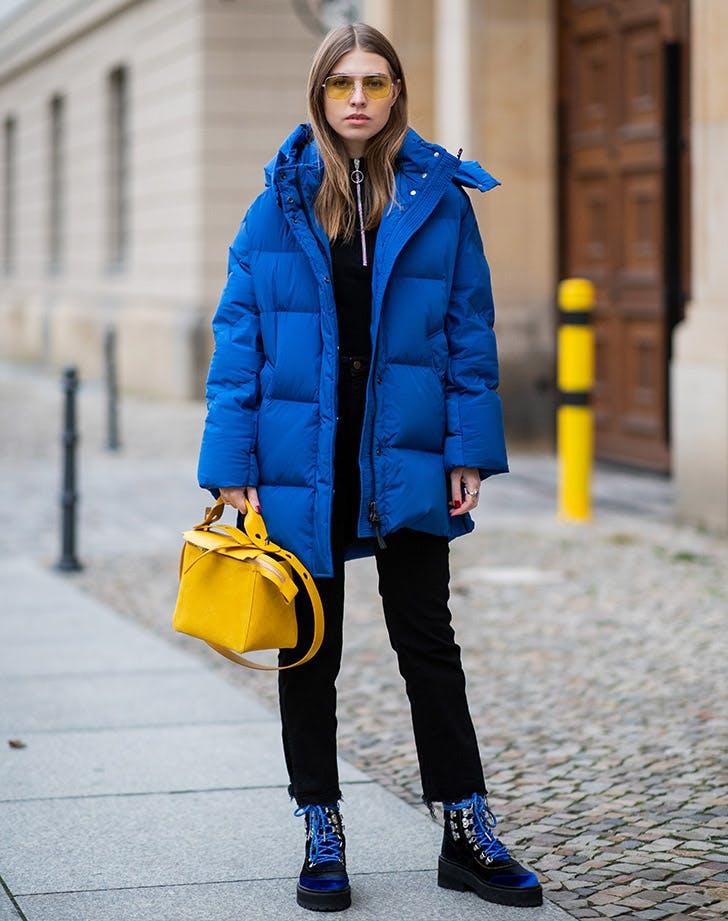 Девушка в черных брюках, ботинки и синий пуховик оверсайз
