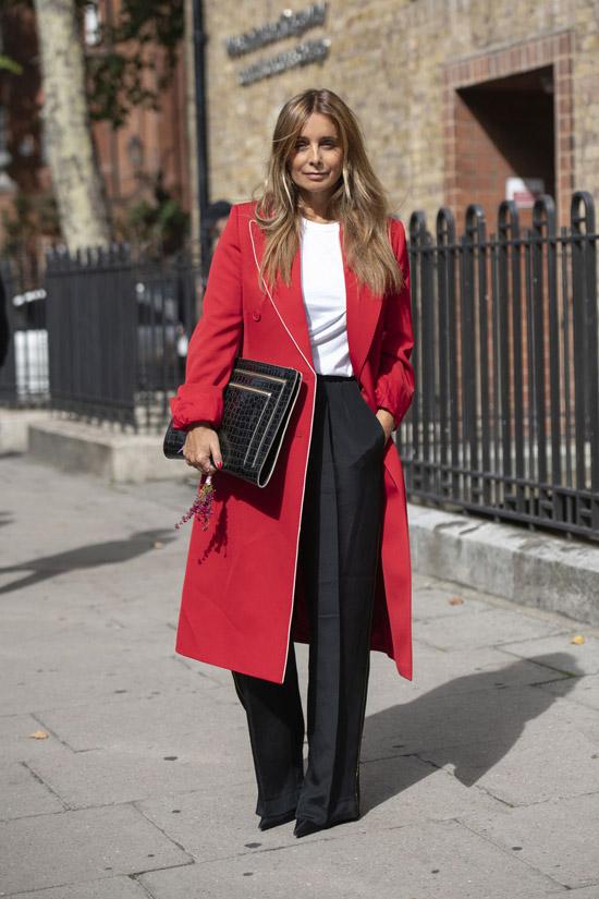 Девушка в черных брюках со стрелками и красном пальто миди