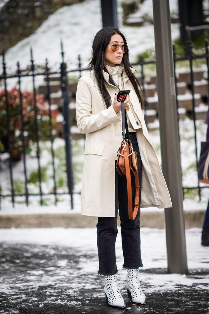 Девушка в черных джнсах, белое пальто и ботильоны