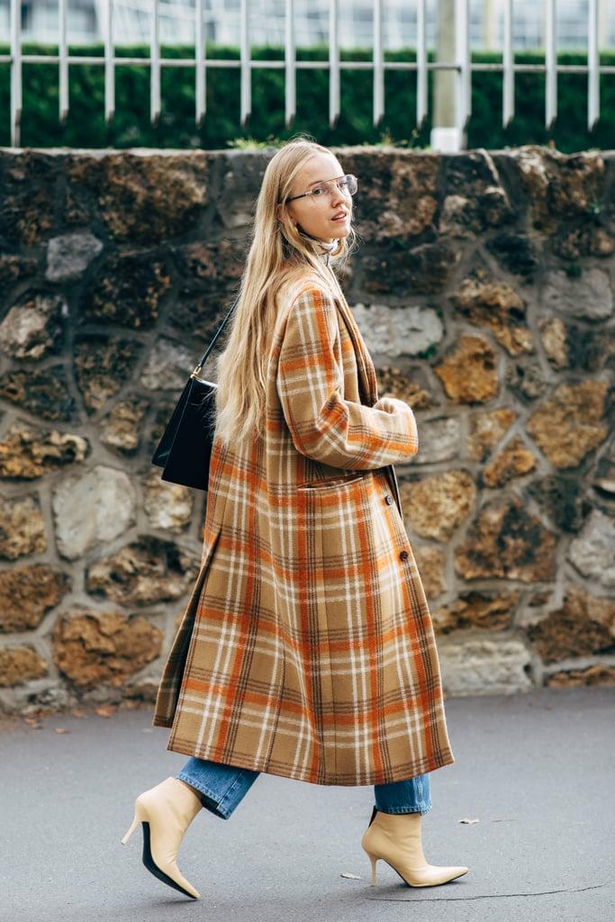 Девушка в длинном пальто в клетку, джинсы и ботильоны на шпильке