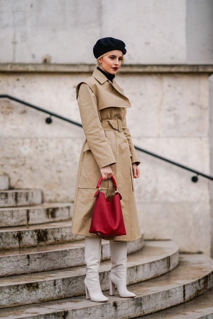 Девушка в бежевом плаще, красная сумка и белые сапоги