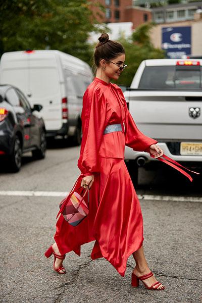 Девушка в красном атласном платье с длинными рукавами