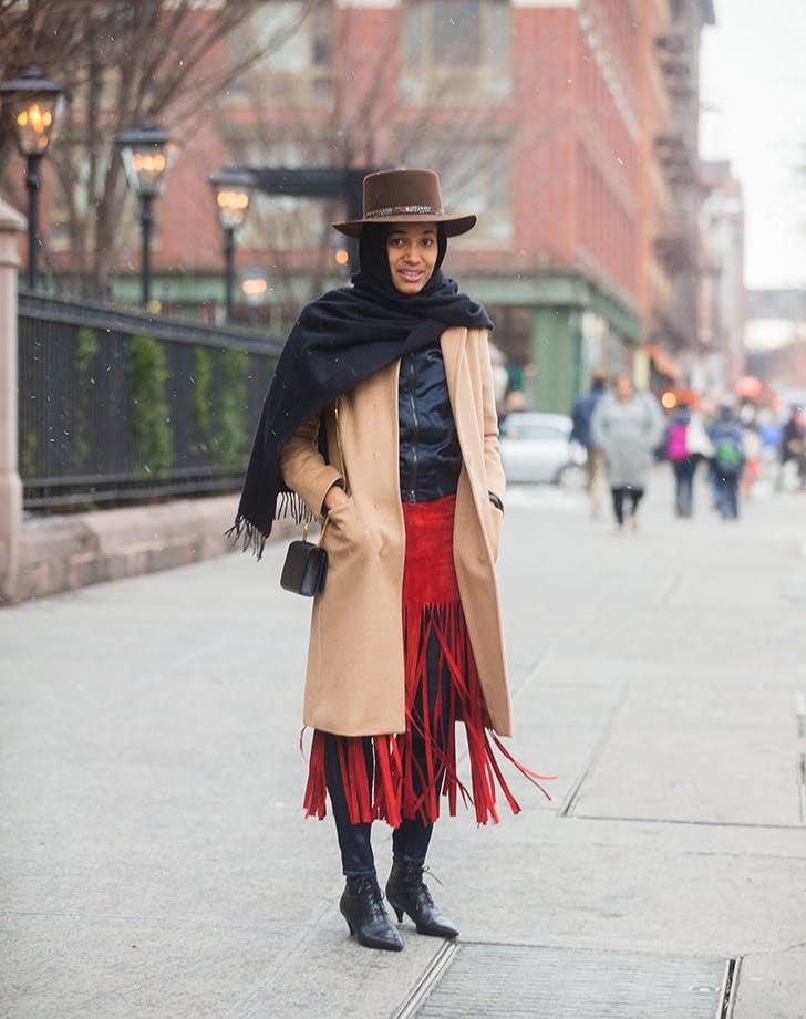Девушка в красной юбке с бахромой, бежевое пальто, черный платок и шляпа