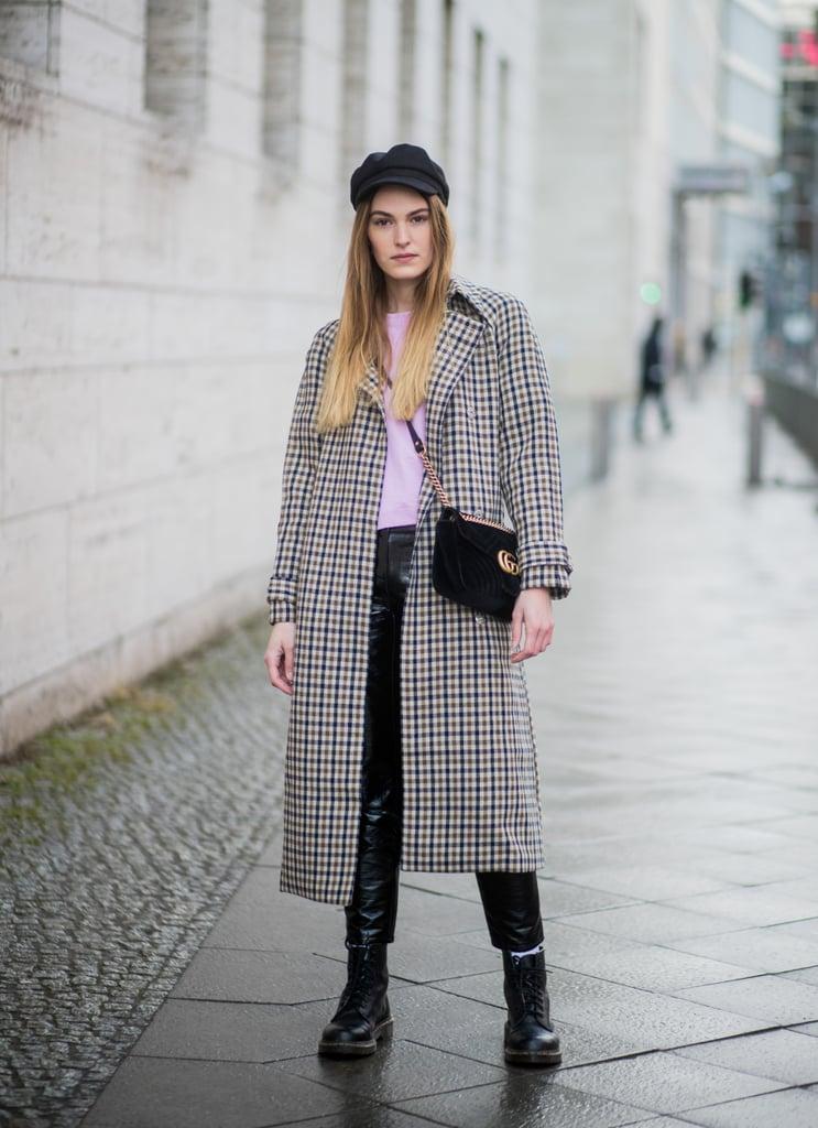 Девушка в пальто в клетку, кожаные леггинсы и черные ботинки
