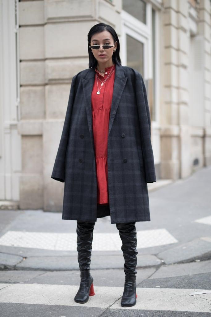 Девушка в пальто в клетку, красное платье и ботфорты