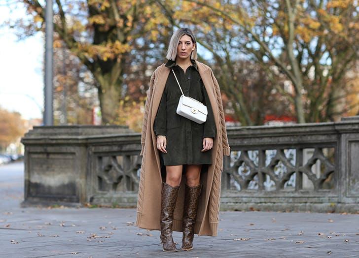Девушка в платье рубашке, коричневое длинное пальто и высокие сапоги