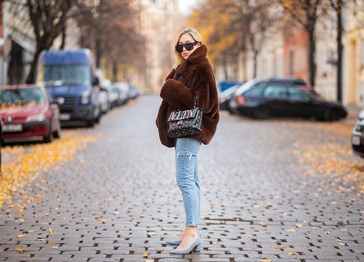 Девушка в рванных джинсах, коричневая куртка и туфли
