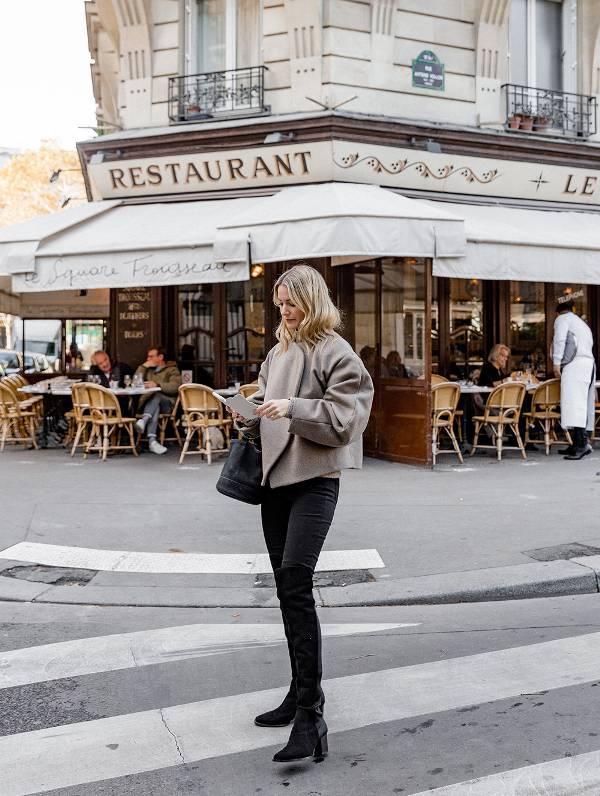 Девушка в серой куртке, джинсы скинни и черные ботфорты