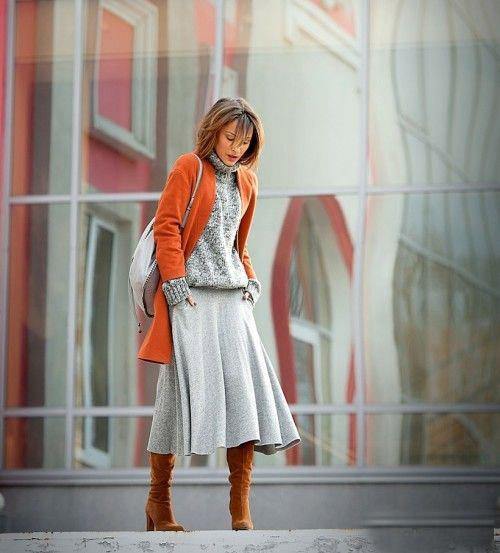 Девушка в серой юбке миди, свитер и оранжевое пальто