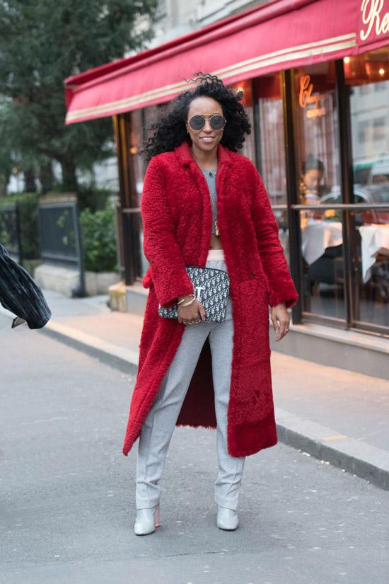 Девушка в серых брюках и красном плюшевом пальто