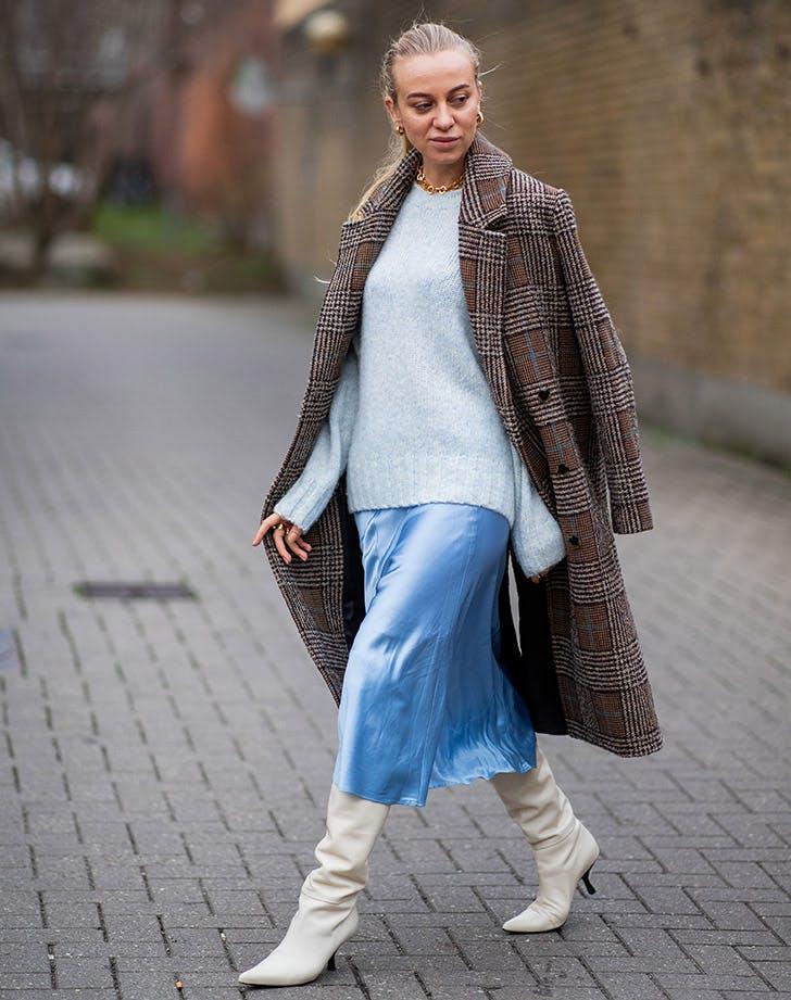 Девушка в шелковой юбке миди, серый свитшот и пальто в клетку