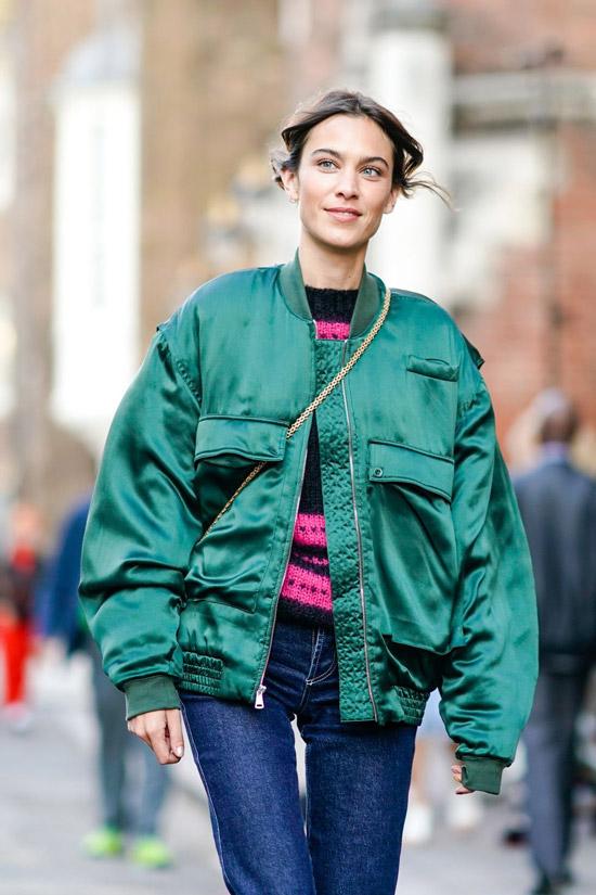 Девушка в синих джинсах и зеленом бомбере
