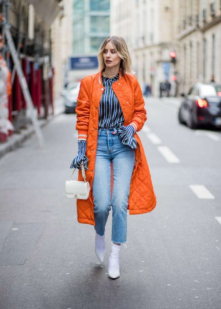 Девушка в укороченных джинсах, оранжевая куртка и белые ботильоны
