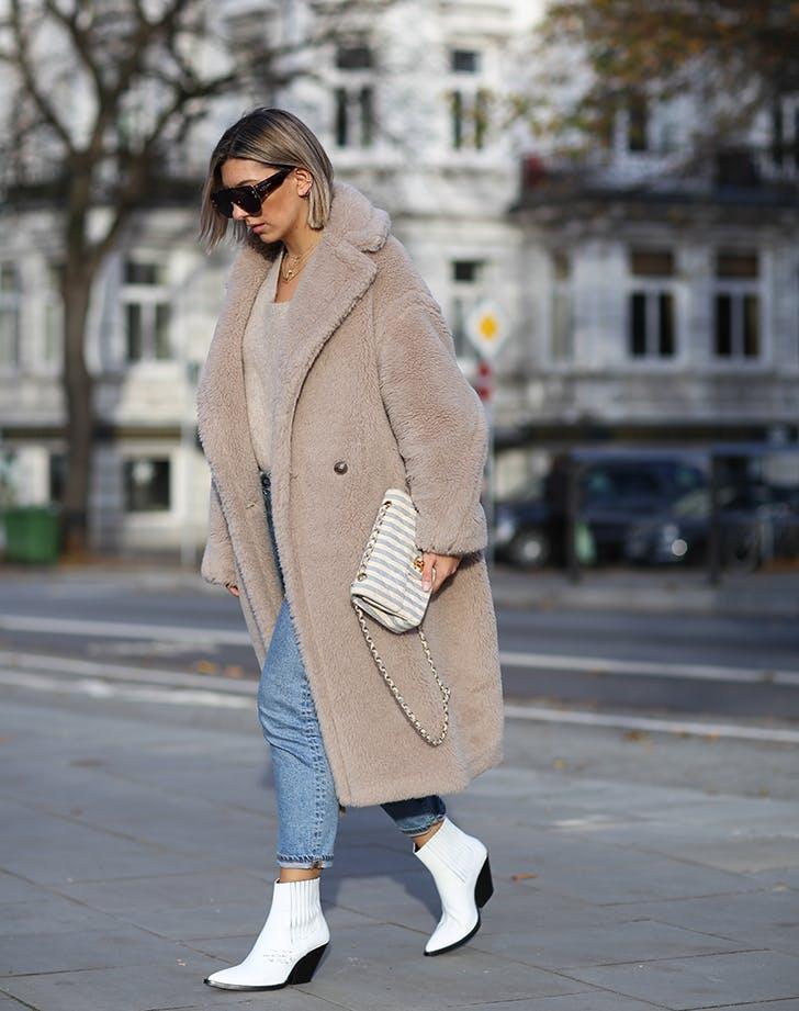 Девушка в укороченных джинсах, плюшевое пальто и белые ботильоны
