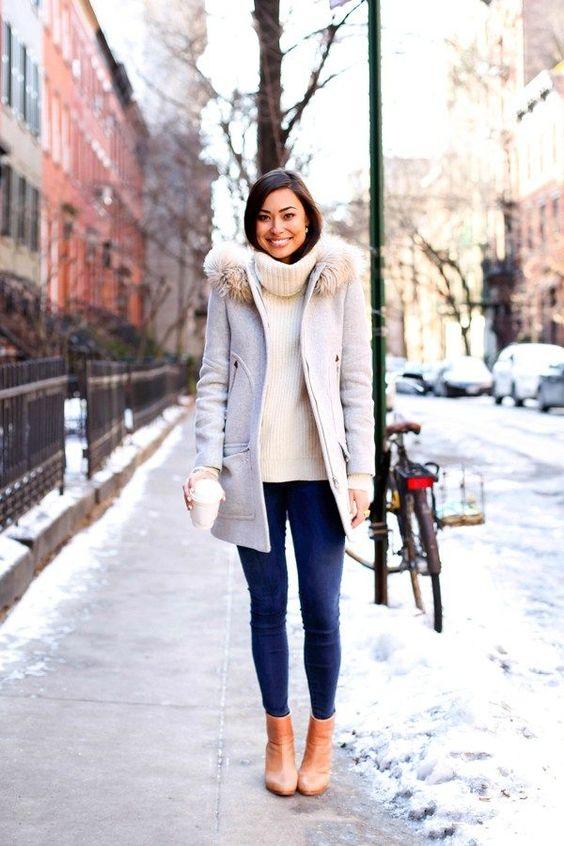 Девушка в узких джинсах, свитер и светлое пальто