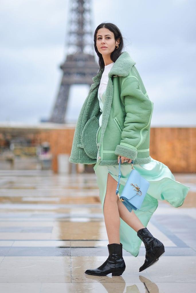 Девушка в зеленой дубленке, легка юбка и черные ковбойские сапоги