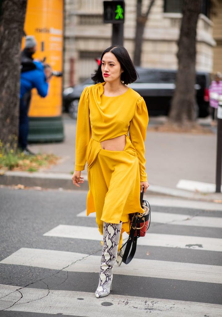 Девушка в желтом платье миди и высоких сапогах из змеиной кожи