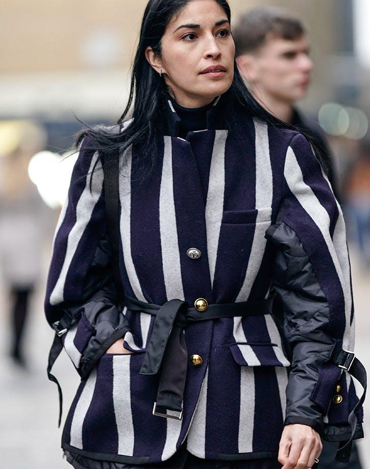 Девушка в зимнем пальто в клетку с поясом