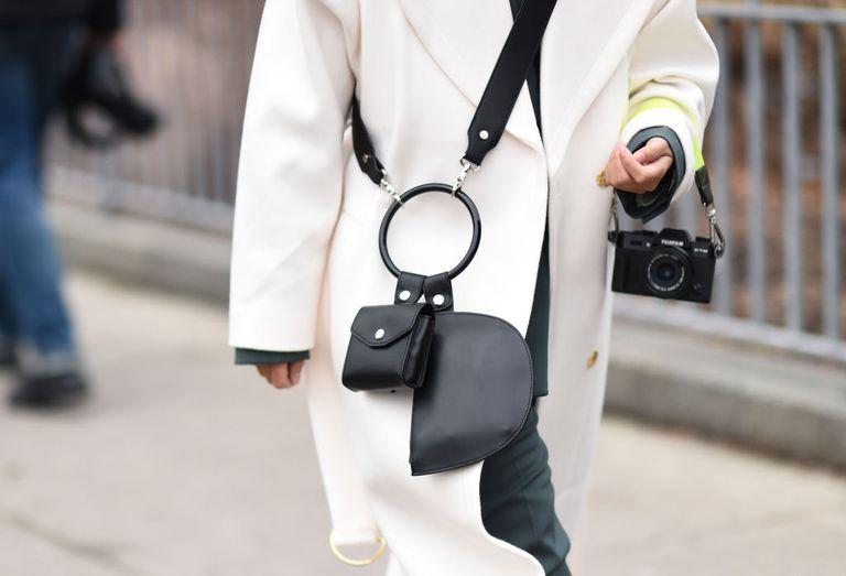 Девушка в белом пальто и черной сумке