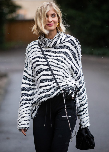 Девушка в черных брюках и свитере в черно белую полоску