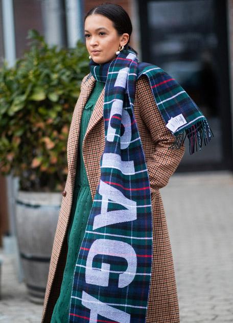 Девушка в коричневом пальто в клетку и большом шарфе с логотипом