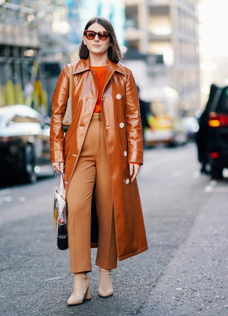 Девушка в коричневых брюках и виниловое кожаное пальто