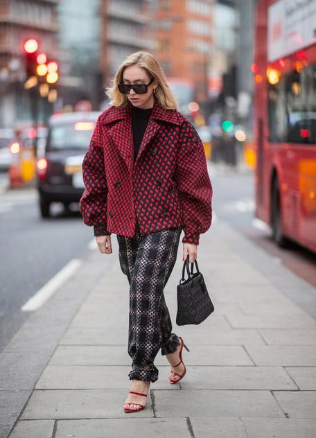 Девушка в красном пальто, брюки в клетку и красные босоножки