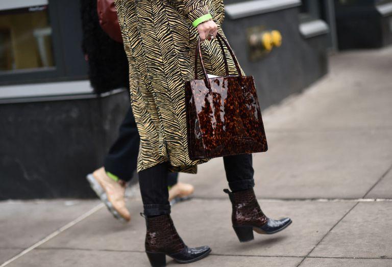 Девушка в пальто, коричневые ботильоны и лакированная сумка