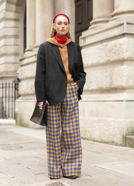 Девушка в широких брюках в клетку, черный пиджак и толстовка