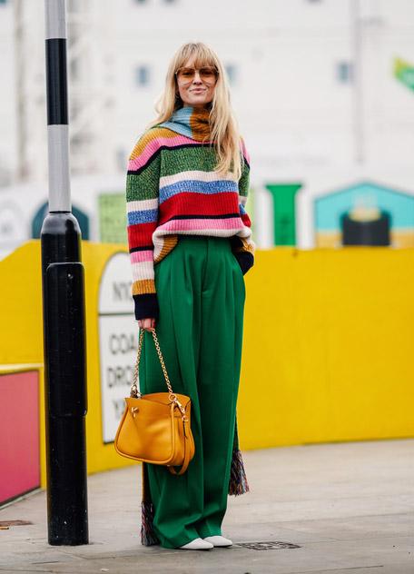 Девушка в широких зеленых брюках и полосатом свитере