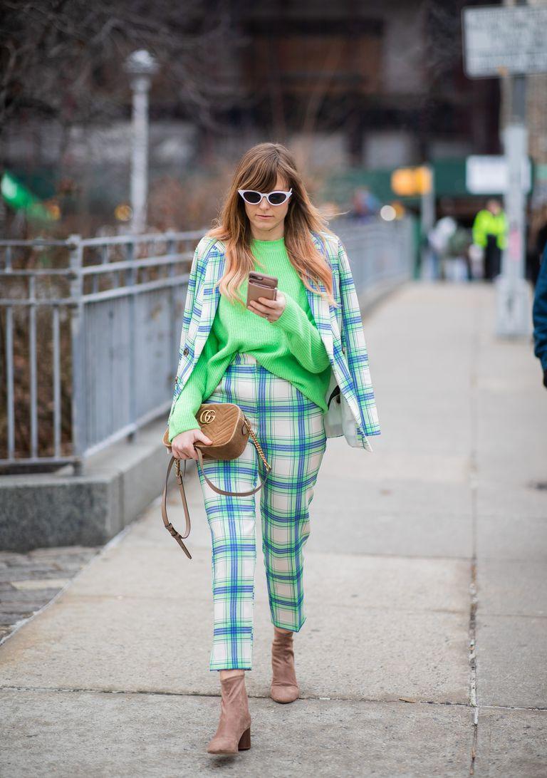 Девушка в светлом костюме в клетку и зеленом свитшоте