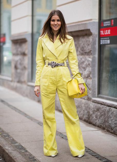 Девушка в желтом костюме с поясом и с желтой сумкой